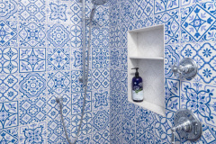 blue and white shower after bathroom remodel. Features Custom casings and hand-made rosettes, tone-on-tone floor tile, vintage-inspired lighting, built in shelving in shower and classic chrome plumbing fixtures.