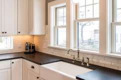 Traditional style kitchen remodel. Factory-style windows and reclaimed wood give textured punch to traditional kitchen addition.  Remodel features additional flex living space, mudroom and powder room.
