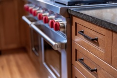 Wooden cabinetry & handles, range in background, countertop  detail image, part of Craftsman style kitchen remodel in St. Paul, MN that includes gourmet kitchen and square island.