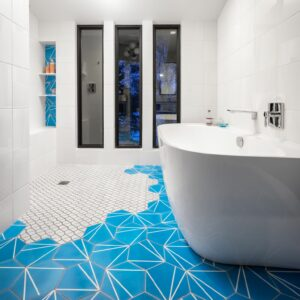 Bathroom with bright cerulean blue floor tiles and geometric shower floor; soaking tub with views to the lake and beyond