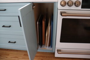 Taller kitchen drawer next to oven with cutting boards and cookie sheets.